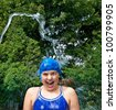 Teenage girl laughing from cold water being squirted on her from a hose. She wears a blue swim suit, bathing cap, swim goggles. Green foliage in background. Square composition, copy space. - stock photo