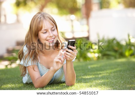 Teenage Girl Laying In Park Using Mobile Phone - stock photo