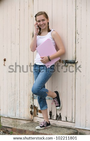 Teenage girl leaning against beach hut talking on phone and holding folder