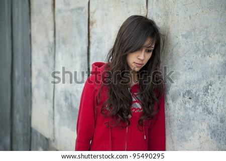 Teenage girl leaning against grunge wall with expression of sadness. - stock photo