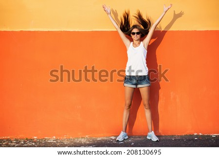 teenage girl leaning against orange wall in urban environment - stock photo
