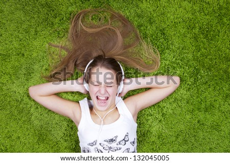 Teenage girl listen the music in headphones and sings, on the green carpet. - stock photo