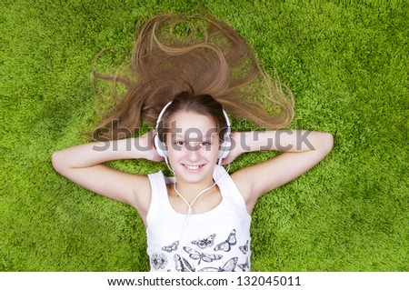 Teenage girl listen the music in headphones and smiling, on the green carpet. - stock photo