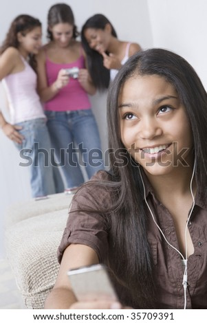 Teenage girl listening to an MP3 player and smiling - stock photo