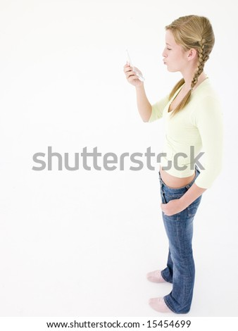 Teenage girl looking at cellular phone and puckering up - stock photo
