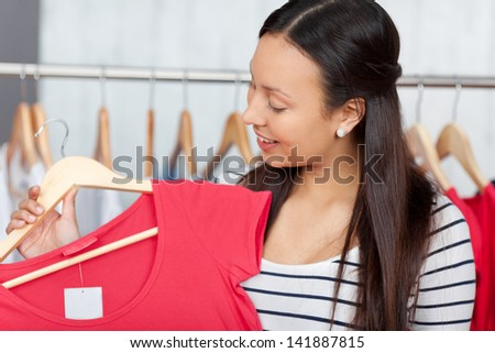 Teenage girl looking at new top in textile shop