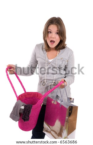 Teenage girl looking shocked at the content of her shopping bag - stock photo