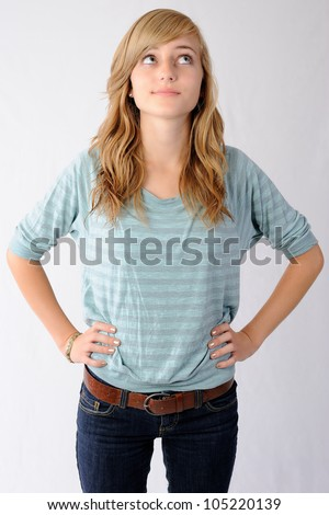 Teenage Girl Looking Up. Thirteen year old girl standing with her hands on her hips looking up and to the side. Note: Not Isolated. - stock photo