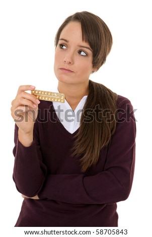 Teenage girl looking worried at contraception pills isolated on white