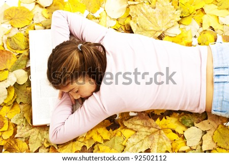 Teenage girl lying down reading book with leaves around - stock photo