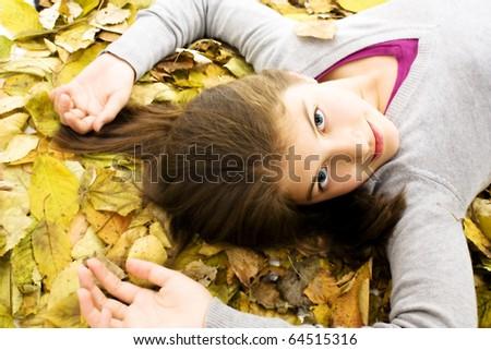Teenage girl lying down with leaves around. - stock photo