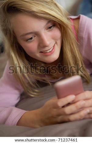 Teenage Girl Lying In Bedroom Using Mobile Phone - stock photo