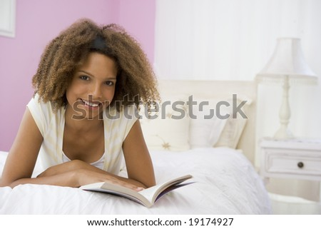 Teenage Girl Lying On Bed Reading A Book - stock photo