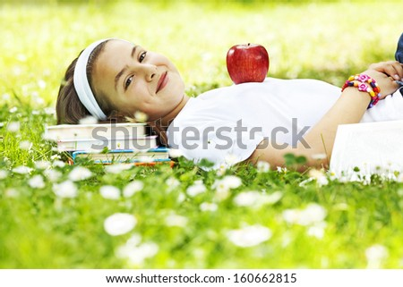 Teenage girl lying on pile of books in park - stock photo