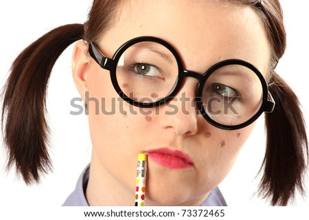Teenage girl made-up like a geek. Holding pencil to lips in thought. - stock photo