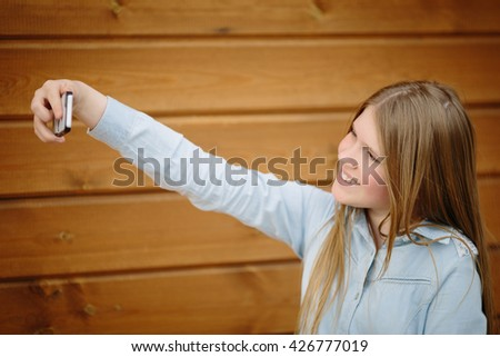 Teenage girl making selfie with a mobile phone on the wooden background open aperture selective focus - stock photo