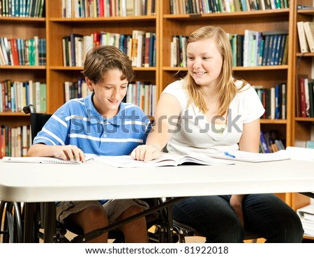 Teenage girl mentoring a younger, disabled boy in the school library. - stock photo