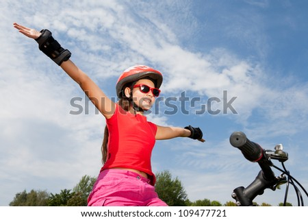 teenage girl on a bicycle with hands up - stock photo