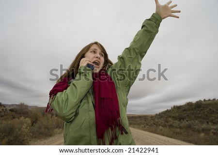 Teenage girl on a desert road, talking on her cell phone - stock photo