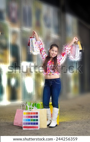 Teenage girl on a shopping spree holding shopping bags.  Illustrating shopping and fashion. - stock photo