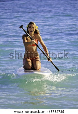 teenage girl on a stand up paddle board in the ocean - stock photo