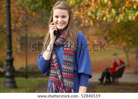 Teenage Girl On Mobile Phone In Autumn Park With Couple On Bench In Background - stock photo