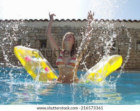 Teenage girl on pool raft splashing water in swimming pool