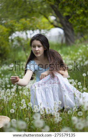 Teenage girl on the field with dandelions