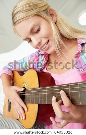 Teenage girl playing acoustic guitar - stock photo