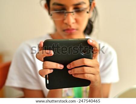 Teenage girl playing game on mobile phone. - stock photo