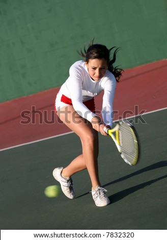 Teenage girl playing tennis - stock photo