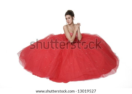 Teenage girl posing in her graduation/prom gown against a white background. - stock photo