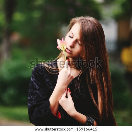 Teenage girl posing with tulip in hands.