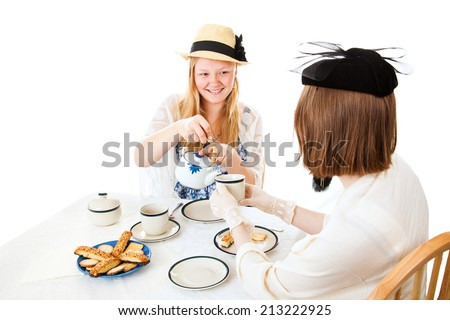Teenage girl pouring a cup for her friend at a formal tea party.  Isolated on white - stock photo
