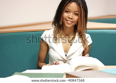 Teenage girl reading a book in the library - stock photo