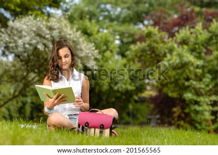 Teenage girl reading book sitting on grass summer park