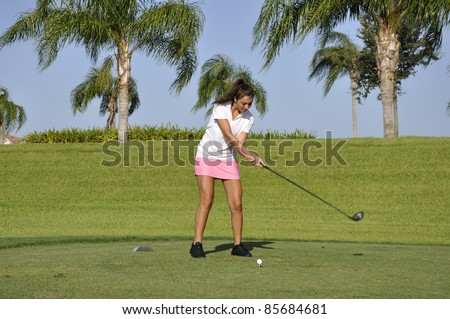 Teenage girl ready to drive a golf ball on a golf course in Naples, Florida - stock photo