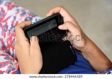 Teenage girl sending message on her mobile phone - stock photo