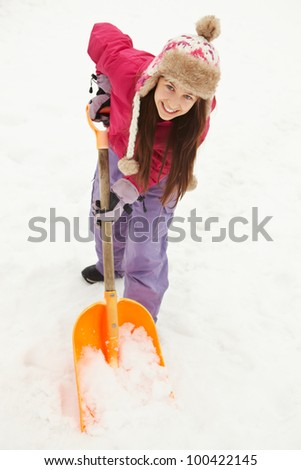 Teenage Girl Shovelling Snow From Path - stock photo