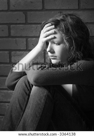 Teenage girl siiting against brick wall in a depressed state - stock photo