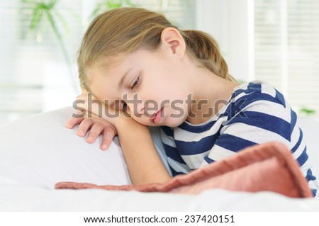 Teenage girl sits in sofa daydreaming - stock photo