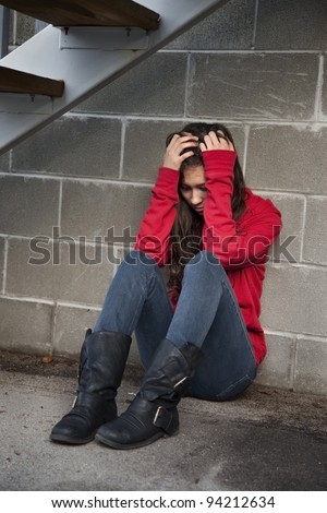 Teenage girl sitting against brick wall in a depressed state. - stock photo