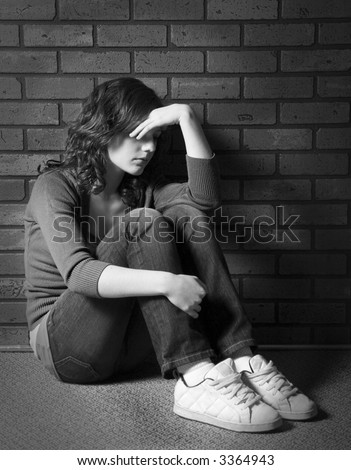 Teenage girl sitting against brick wall in depressed state - stock photo