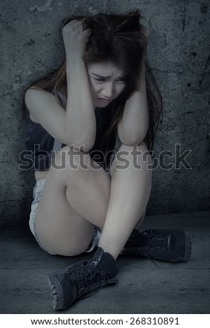 Teenage girl sitting alone and looks depressed, shot against a dark background - stock photo