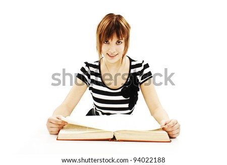 Teenage girl sitting at the desk and reading book. Isolated on white background - stock photo