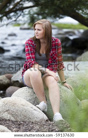 Teenage girl sitting at the water with a worried expression - stock photo