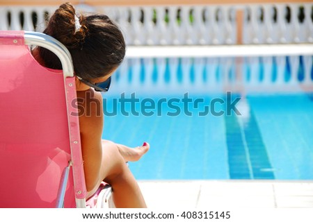 teenage girl sitting by the blue clear transparent swimming pool - stock photo