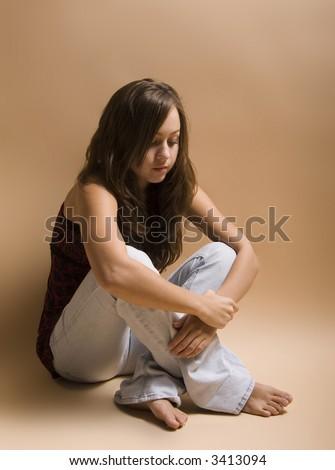 Teenage girl sitting cross-legged in depressed state - stock photo