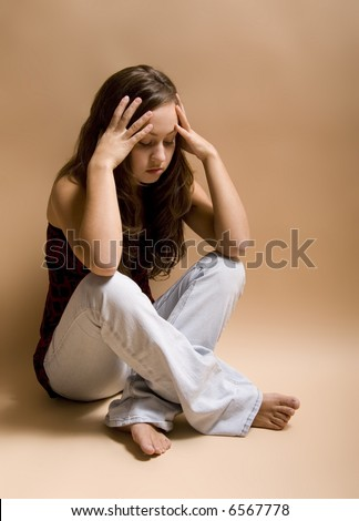 Teenage girl sitting cross-legged on floor in a depressed state. - stock photo