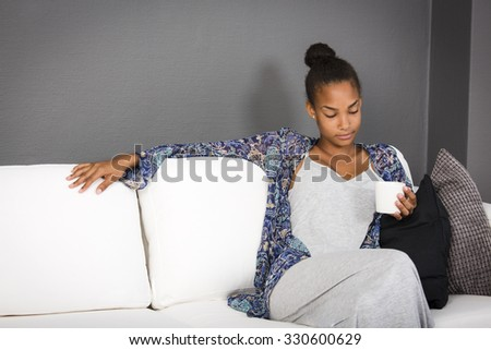 Teenage girl sitting in a couch with a cup of coffee or tea in her hand.